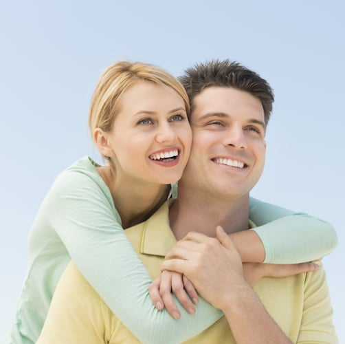 Woman hugging man around shoulders